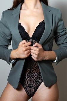 Studioporträtaufnahme einer schönen frau, die mit dessous und jacke posiert