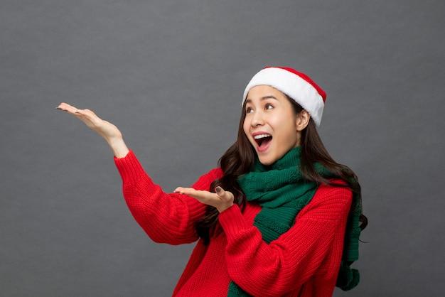 Studioportrait der asiatischen frau weihnachtskleidung mit ihren armen anhebend angehoben