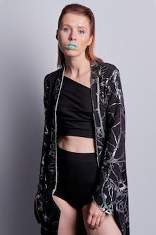 Studioportrait des attraktiven europäischen models in hoch tailliertem slip, kurzer bluse und schwarzem mantel mit print