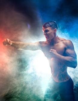 Studioportrait des kämpfens des muskulösen mannes im rauche