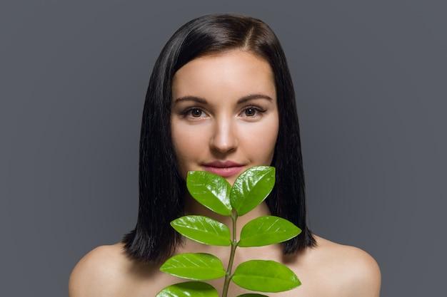 Studioschönheitsporträt des jungen brunette mit perfekter haut des natürlichen make-up mit grünem exotischem blatt