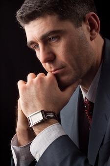 Studuo schuss des denkenden geschäftsmannes, der anzug und krawatte mit teurer uhr trägt