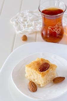 Stück basbousa traditioneller arabischer grieß-kuchen mit nuss-orangenblüten-wasser-vertikalem kopienraum weißhintergrund