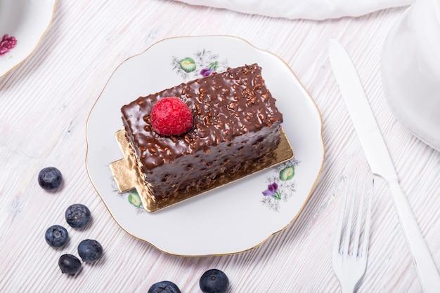 Stück beerenschokoladenkuchen verziert mit frischer erdbeere auf weißem holzhintergrund