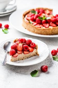 Stück beerentörtchen mit himbeeren, erdbeeren und sahne auf weißer platte