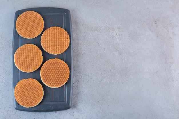 Stück braune hausgemachte stroopwaffel-snacks in einem holzbrett.