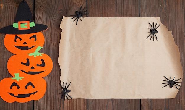 Stück braunes papier und orange kürbisfilzfiguren