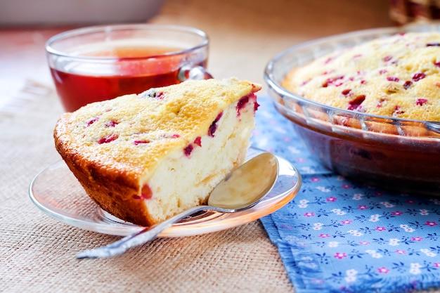 Stück cowberry pie auf glasplatte und tasse tee