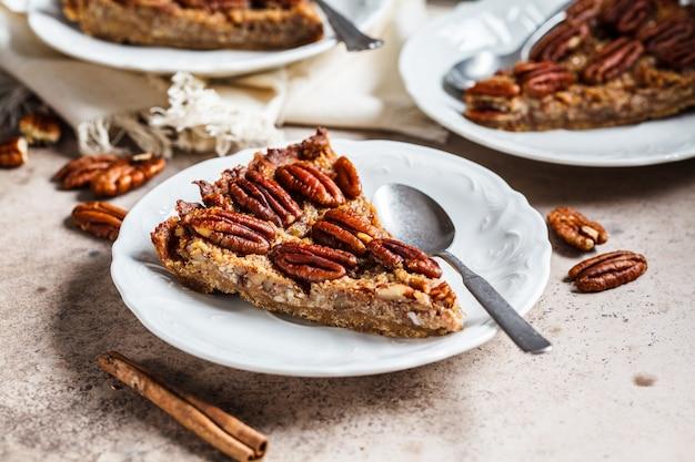 Stück der pekannuss-torte auf grau-braunem hintergrund. veganes dessertkonzept.