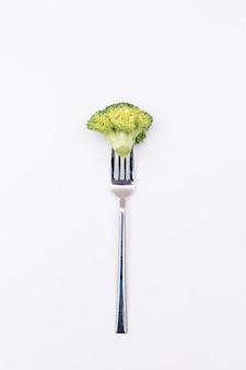 Stück frischer brokkoli auf der gabel lokalisiert auf weißer oberfläche