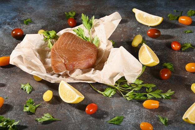 Stück geräucherter thunfisch auf braunem papier, nahe gemüse.