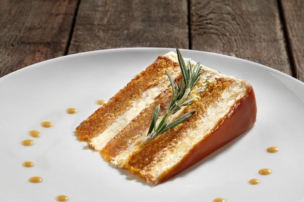 Stück geschichteter honigkuchen mit sauerrahm und karamellsauce