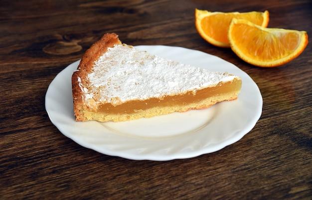 Stück hausgemachte torte mit zitronen-orangen-füllung auf einem holztisch