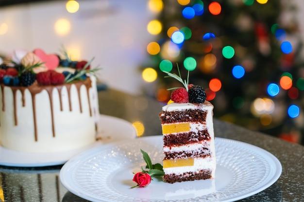 Stück hausgemachten weihnachtskuchen whis obst. frohes neues jahr und frohe weihnachten hintergrund. winterdekorationen über dunklem hintergrund mit defokussiertem weihnachtsbaumlicht. selektiver fokus.
