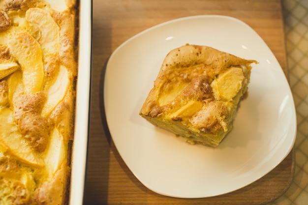 Stück hausgemachter apfelkuchen auf weißem teller