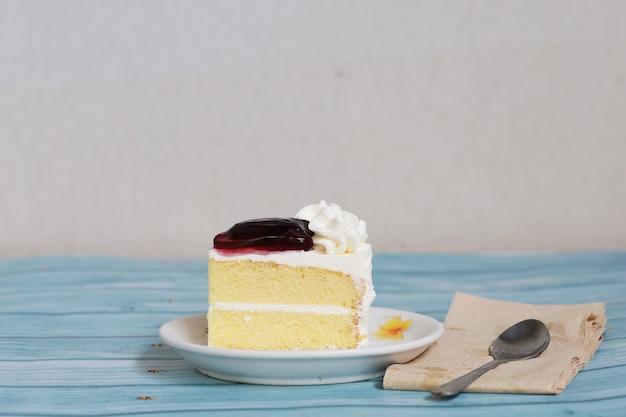 Stück hausgemachter blaubeerkuchen auf weißen teller und löffel, süße dessertbäckerei-fruchtcreme und käsekuchen