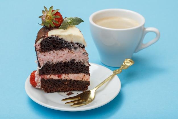 Stück hausgemachter schokoladenkuchen verziert mit frischen erdbeeren und minzblättern auf weißem teller mit gabel und tasse kaffee auf blauem hintergrund.