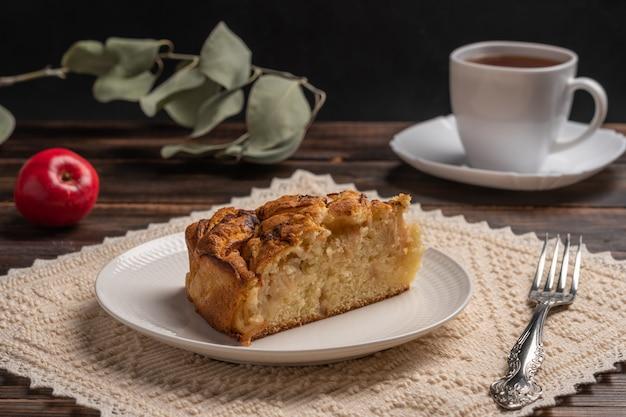 Stück hausgemachter traditioneller kornischer apfelkuchen auf einem weißen teller mit einer gabel auf einer serviette