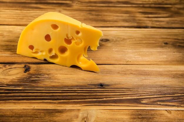 Stück käse auf dem hölzernen hintergrund