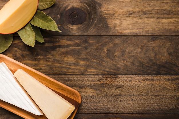 Stück käse auf hölzernem behälter mit lorbeer verlässt gegen holztisch