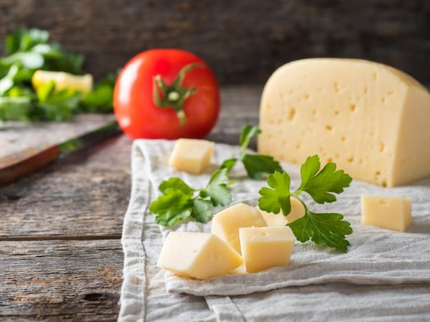 Stück käse mit petersilie, tomaten auf einem leinentuch rustikaler hölzerner hintergrund.