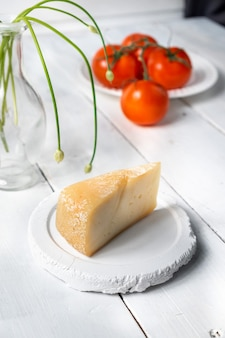 Stück käse mit tomaten auf einem holzbrett, käseproben, käse mit einem schnitt