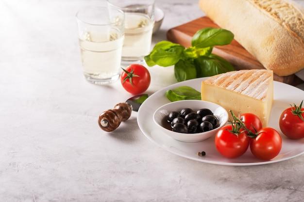 Stück käse mit tomaten und schwarzen oliven auf einem teller