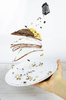Stück käsekuchen mit braunen kuchen und weißer sahne, die über dem weißen teller fliegen