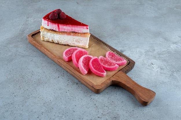 Stück käsekuchen mit marmeladen auf holzbrett. foto in hoher qualität