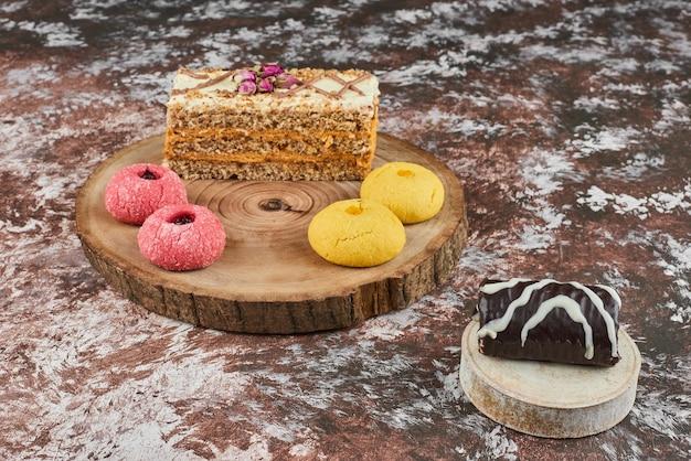 Stück karottenkuchen mit brownies auf einem holzbrett.