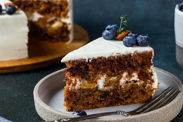 Stück karottenkuchen mit walnüssen und blaubeere auf dunklem holzhintergrund. lokales essen. traditioneller amerikanischer kuchen. kuchen zum erntedankfest. weihnachtskuchen.