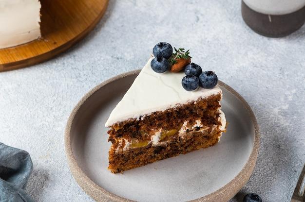 Stück karottenkuchen mit walnüssen und blaubeeren auf hellem hintergrund. lokales essen. traditioneller amerikanischer kuchen. kuchen zum erntedankfest. herbstkuchen.