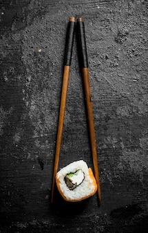Stück köstliche japanische sushi-rollen mit stöcken. auf schwarzer rustikaler oberfläche