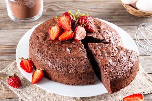 Stück köstlicher frischer hausgemachter schokoladenbiskuitkuchen mit erdbeere auf holztisch