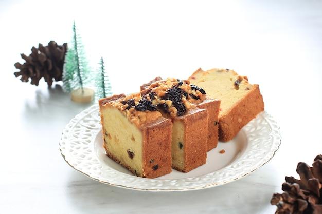 Stück köstlicher hausgemachter englischer obstkuchen-loaf-pudding mit getrockneten gemischten früchten, sultaninen, rosinen und gehackter mandel. serviert während der weihnachtsfeier oder silvester