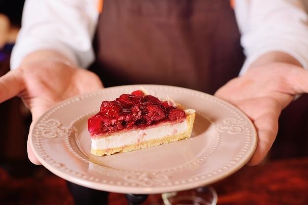 Stück köstlicher kuchen oder käsekuchen mit himbeeren auf einer plattennahaufnahme