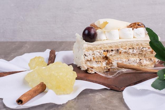 Stück kuchen auf holzbrett mit tischdecke und süßigkeiten.