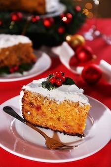 Stück kuchen auf teller mit gabel auf tisch mit weihnachtsdekorationsoberfläche