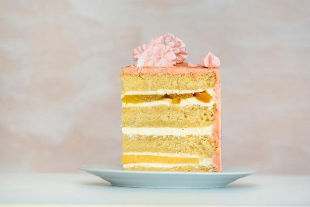 Stück kuchen auf weißem teller. biskuitkuchen und vanillefruchtcreme.