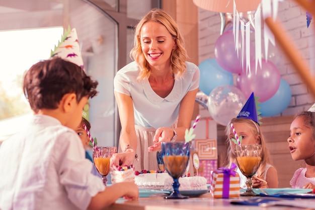 Stück kuchen. fröhliche junge frau, die lächelt und dem jungen auf der geburtstagsfeier ein stück kuchen gibt