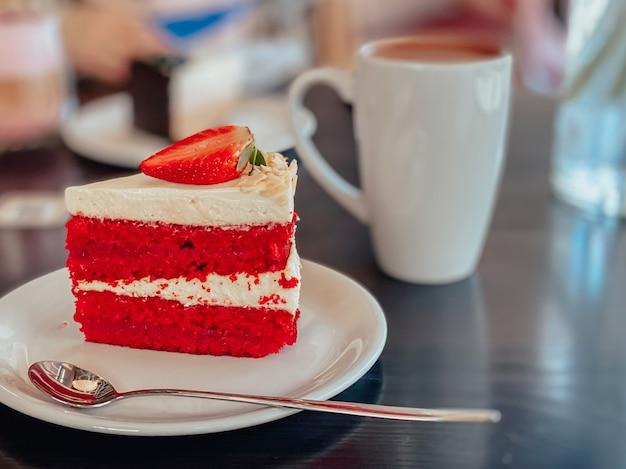 Stück kuchen in weißen und roten farben mit biskuitkuchen, sahne und dekoration auf dem kuchen in form von erdbeeren auf dem tisch im restaurant.