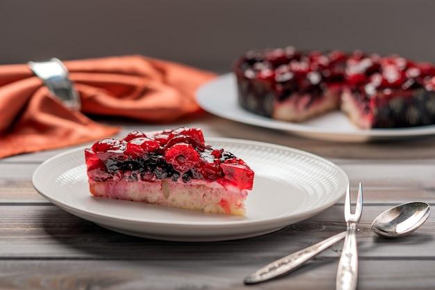 Stück kuchen mit beeren himbeer johannisbeere erdbeere auf einem weißen teller neben dessertlöffel und