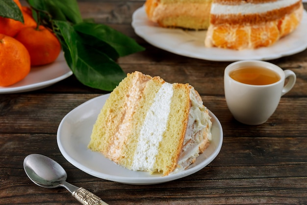 Stück kuchen mit grünem tee und frischer mandarine auf holztisch