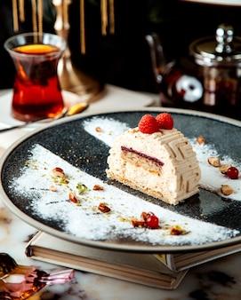 Stück kuchen mit himbeeren und einem glas tee auf dem tisch dekoriert