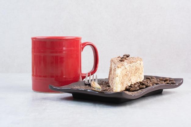 Stück kuchen mit kaffeebohnen und tasse kaffee. foto in hoher qualität