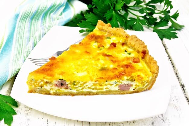 Stück kuchen mit kürbis und speck, gefüllt mit milch mit eiern und käse in einem teller, petersilie, ein handtuch auf dem hintergrund eines hellen holzbretts
