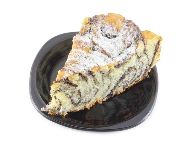 Stück kuchen mit mohnfüllung und mit puderzucker auf einer schwarzen untertasse bestreut auf weiß bestreut