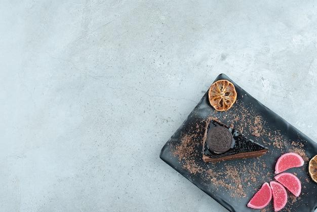 Stück kuchen mit orangenscheiben und marmeladen auf schwarzem teller. foto in hoher qualität
