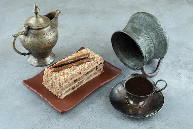Stück kuchen mit tasse tee und teetasse auf marmoroberfläche.
