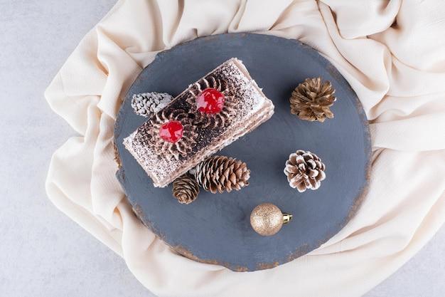 Stück kuchen mit weihnachtsschmuck auf holzstück. foto in hoher qualität